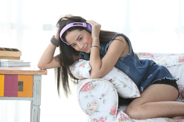 young woman relaxing on an armchair at home, listening to music