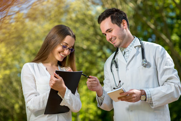 Young doctor with assistant speaking in the park.