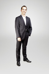 Young man in suit posing on gray background