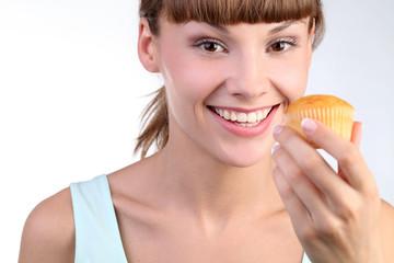 Улыбающаяся девушка с кексом в руке