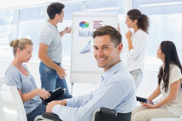 Casual businessman in wheelchair smiling at camera during presen