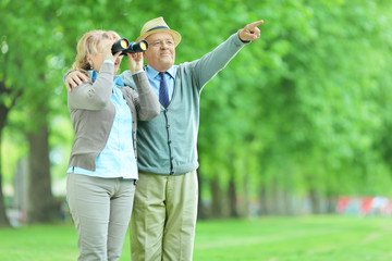 Woman looking through binoculars with her husband