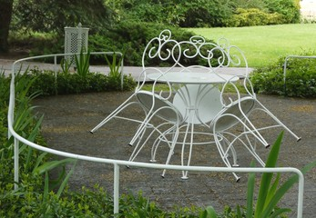 Three ornamented white iron park chairs leant at table