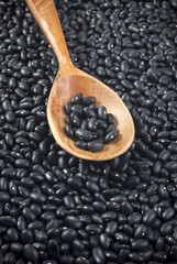 Black beans in wooden spoon