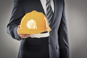 Young foreman in business suit holding yellow helmet