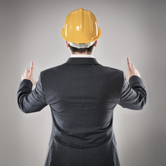 Man architect in hardhat showing, pointing at copy space.