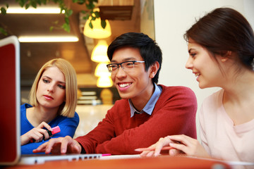 Young happy students using laptop together