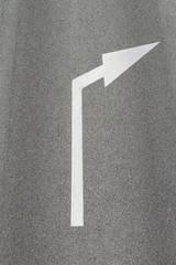 arrow on asphalt showing traffic where to go