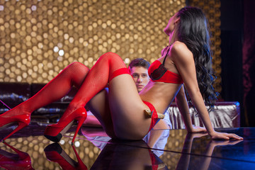 Sexy striptease dancer dancing in front of man in red lingerie