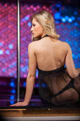 Back view of sexy blond striptease dancer.