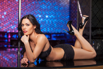 Sexy brunet dancer laying on the stage.