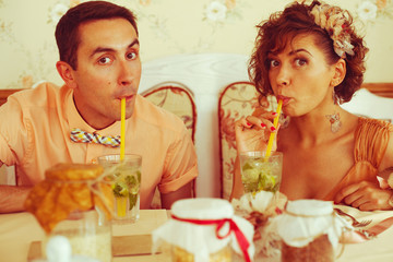 Happy marriage concept. Couple of hipsters drinking mojito