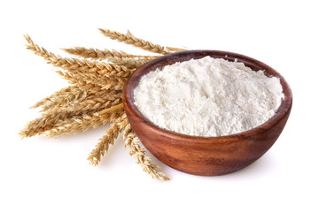 flour with wheat in a wooden bowl on a white background
