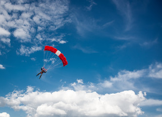 Parachutist over cloudy sky background