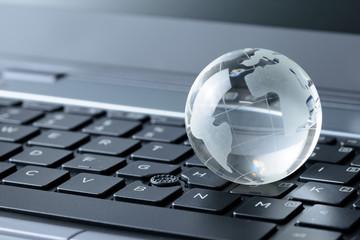 Glass globe on laptop keyboard