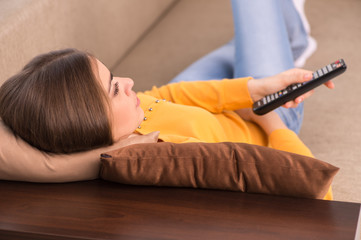 young woman lying on sofa and watching tv.