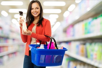 Beautiful woman with basket full  of cleanser in a shop