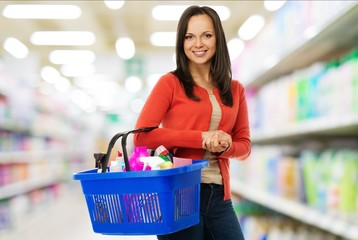 Beautiful woman with basket full of cleansers in a shop