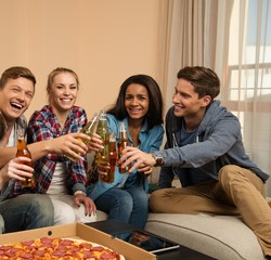 Group of young friends with pizza and bottles of drink