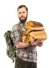 Handsome traveler with backpack and logs for bonfire