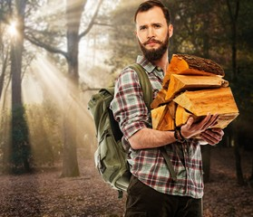 Handsome traveler with backpack in autumnal forest
