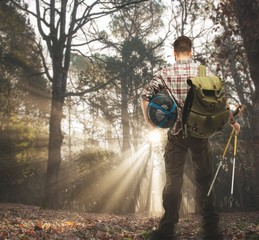 Handsome traveler with backpack and hiking poles in forest