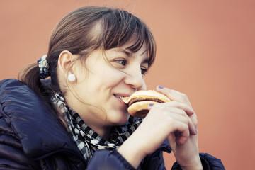 Teenage girl eating a burger