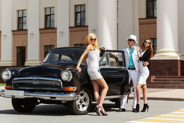 Young fashion people at the retro car