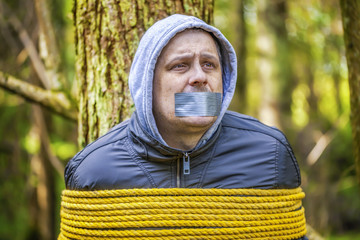 Man with tape on mouth tied to the tree in the forest