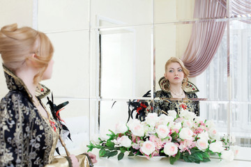 Young actress looking at her reflection in mirror