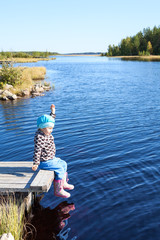 Small child sitting on wooden footbridge at lake