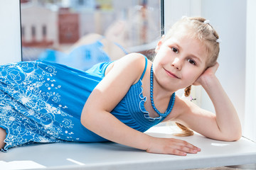 Joyous Caucasian small girl laying on window in sun light