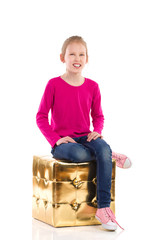 Smiling girl is sitting on a gold pouffe.