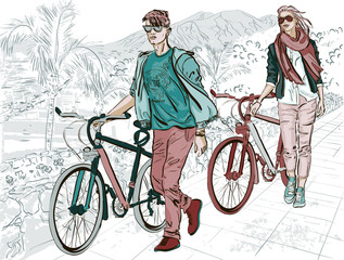 young couple walking on embankment with bicycles