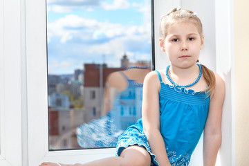 Calm pretty girl in blue dress sitting on window sill