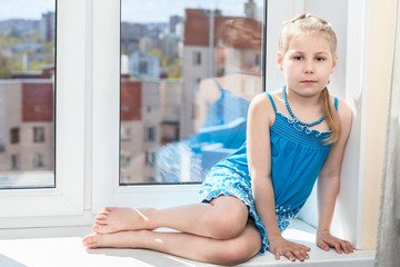 Young child sitting on white window sill in sun light