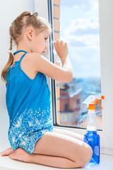Girl cleaning a window with a cloth and detergent