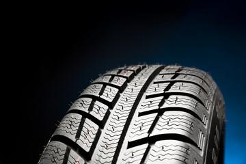 Winter tire on black background