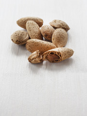 whole and broken almonds on white wooden table