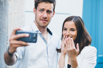 Young couple taking a selfie after engagement. Man is having sec