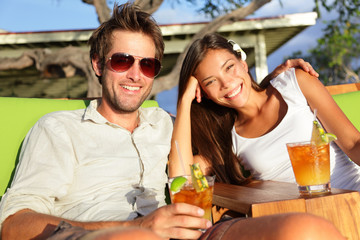 Couple drinking alcohol at beach club having fun