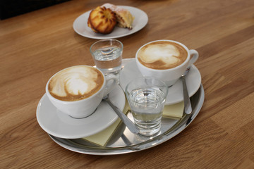Glasses of coffee with water on tray