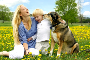 Laughing Mother and Child Playing with Dog