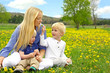 Mother and Children Sitting Outside in Dandelion Flower Meadow