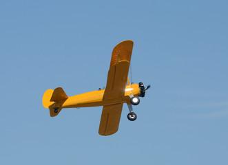 Old yellow biplane in flight