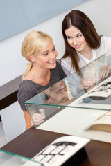 Two girls looking at window case with jewelry at jeweler's shop