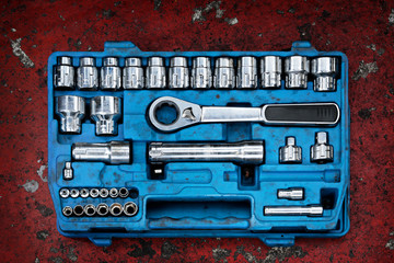 Tools in a blue toolbox on a red background