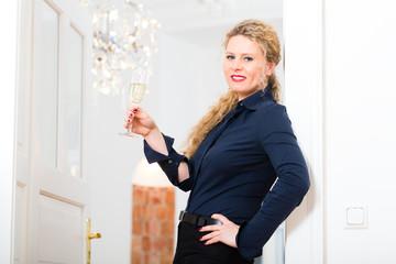Feierabend - junge Frau daheim mit Sektglas