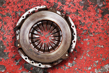 an old worn out vehicle clutch on a red background