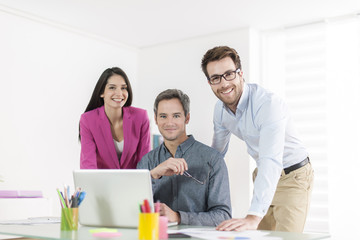 3 colleagues talking about a project in front a computer